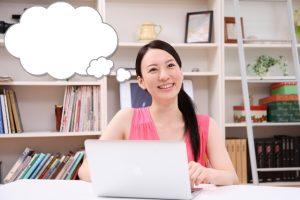 パソコンを見て考えてる女性